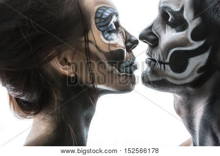 Delightful couple with halloween body-art on the white background in the studio. Their eyes are closed and faces are close to each other. Close-up horizontal photo.