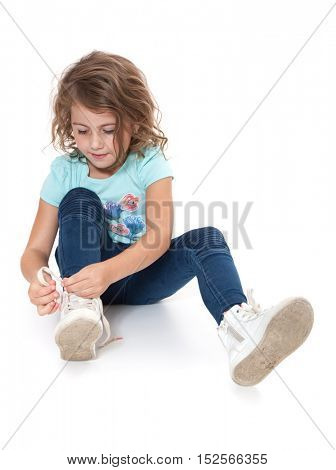 Little girl ties her shoes. All on white background.