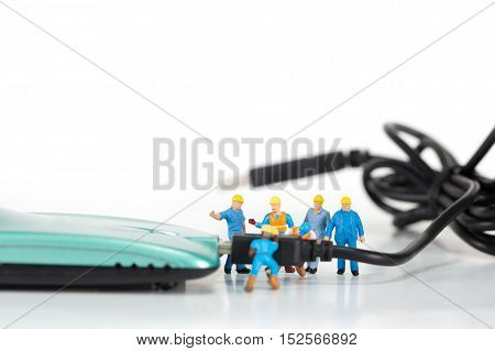Selective focus of miniature engineer and worker plugin or install antenna of wireless router as technology communication and network concept.