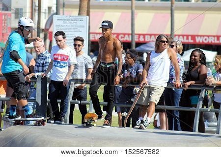 Venice Beach, California, 10/15/16--Diverse group of skateboarders gathers at Venice Beach Skate Park while tourists watch the action.
