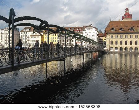 21st of December 2013: people walking over the bridge across the lake in a cold winter day in Luzern Switzerland