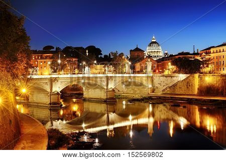 Rome Italy - scenic view of a bridge over Tiber river and St. Peter's Basilica dome in Vatican at night