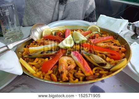 Noodle paella with seafood a bowl on a table