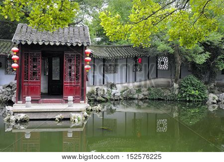 Chinese architecture and a pond within a traditional Chinese Garden in Tongli Town scenic area in Jiangsu Province China.