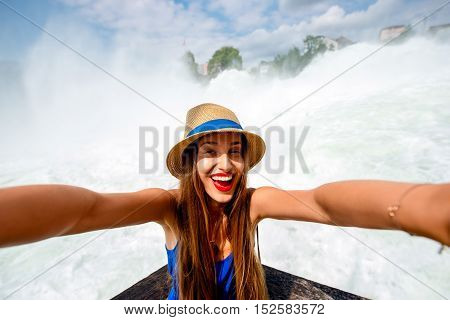 Excited female tourist making self portrait in front of the famous Rhine waterfall. Woman having a great vacation in Switzerland