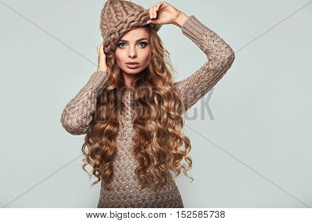 Portrait of beautiful thoughtful blond woman with long hair brown sweater and hat
