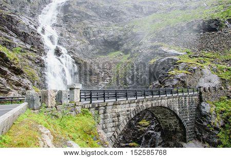 Stone bridge in the mountains. Waterfall near the serpentine. Trollstigen