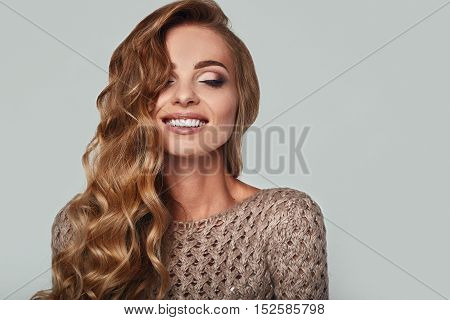 Portrait of beautiful smiling blond woman with long hair brown sweater