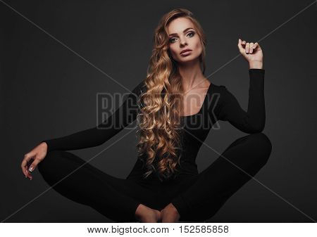 Studio portrait of a sexy long hair blonde in black yoga outfit