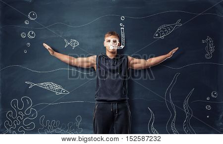 Muscled young man with extended arms and drawn swimming mask and snorkel standing on the backround of drawn underwater world. Scuba diving. Aqualung.