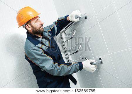 Plumber service. worker installing towel warmer