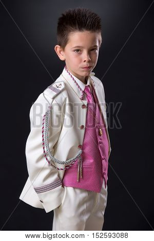 Young Boy Standing Looking Seriously In His First Holy Communion