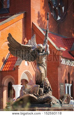 Minsk, Belarus - May 20, 2015: Statue Of Archangel Michael With Outstretched Wings, Thrusting Spear Into Dragon near Red Catholic Church Of St. Simon And St. Helena On Independence Square In Minsk, Belarus