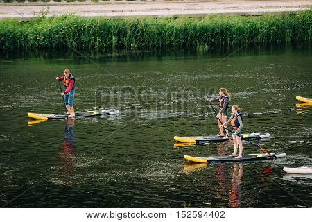 Vilnius, Lithuania - July 08, 2016: Three Young People Stand Up Paddling SUP Or Standup Paddle Boarding On Neris River