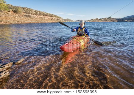 senior male is paddling  a mountain lake Horsetooth Reservoir) - recreation concept