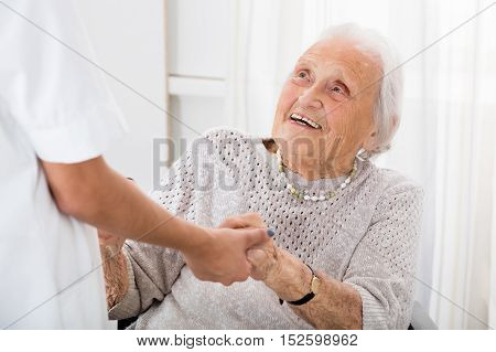Happy Senior Patient Holding Hands Of Female Doctor In Hospital