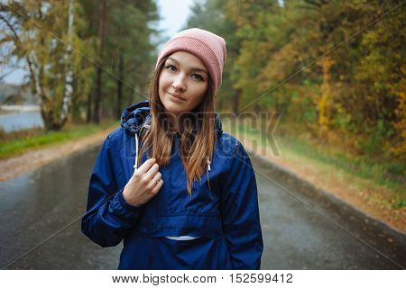 Stylish Sporty Brunette Woman In Trendy Urban Outwear Posing In Rainy Autumn Weather On The Outdoors