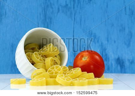 A bowl of wagon wheel or Rotelle pasta with a tomato on a blue bakground selective focus with copy space.