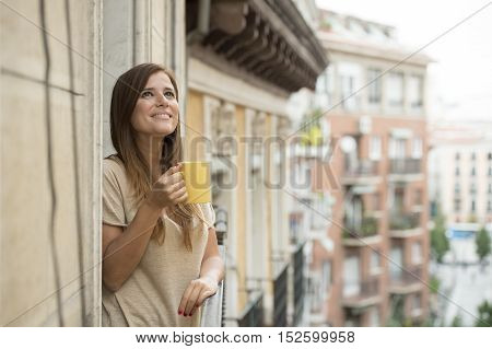 young beautiful woman on her 30s relaxed and cheerful drinking hot tea or coffee cup at apartment balcony terrace with an urban view looking happy and smiling cheerful