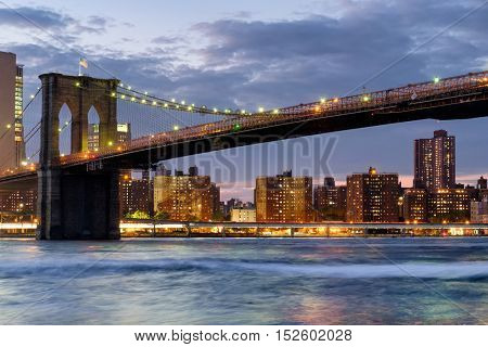 The Brooklyn Bridge in New York City at sunset with reflections on the river