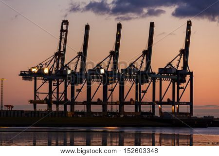 Sunset or sunrise behind cranes at a shipping container port or harbor