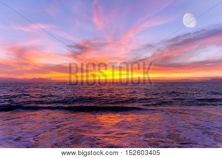 Sunset ocean moon is a colorful scenic ocean sunset setting with the moon rising in the sky.