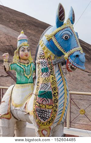 Madurai India - October 21 2013: Statue of young woman sitting of horse. She has no legs. Beige mountain rock as background. All colorful statues at his shrine of Karuppana Sami near Nagamalai village.