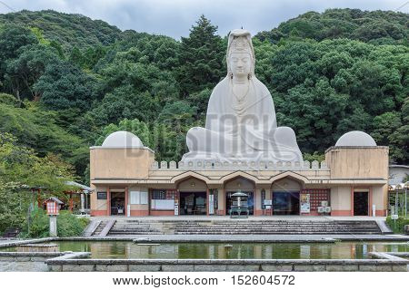 Kyoto Japan - September 19 2016: The Ryozen Kannon WW II Memorial shrine is set against forested hills. The giant statue of goddess Kannon dominates a documentation center.