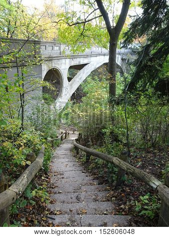 Rustic stone stairway leads down to Ravine Trail under historic Arch Bridge in the woods of Lake Park, Milwaukee, Wisconsin USA on a mid fall afternoon.