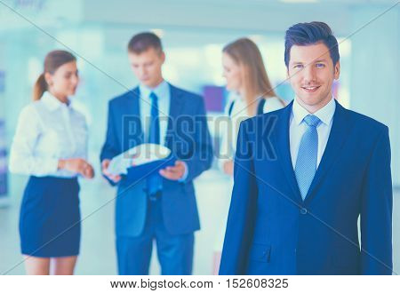 Young businessman with team mates discussing in the background