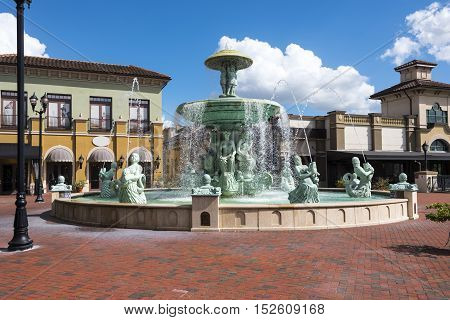 Stone Water Fountain Statue of a green people holding a large fish acting as water spouts