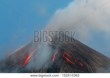 Volcanic landscape of Kamchatka Peninsula: active Klyuchevskaya Sopka view of top of a volcanic eruption - lava flows on of volcano; plume of gas steam and ash from crater. Russian Far East Klyuchevskaya Group of Volcanoes.