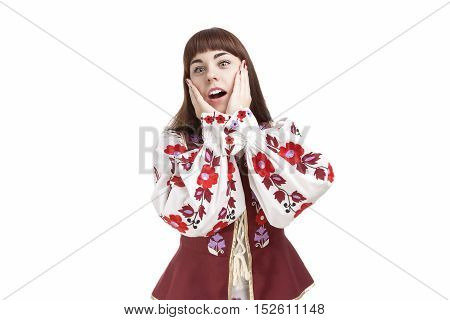 Natural Portrait of Caucasian Brunette Female Posing in National Flowery Dress. Showing Exclamation Touching Cheeks. Horizontal Image Orientation