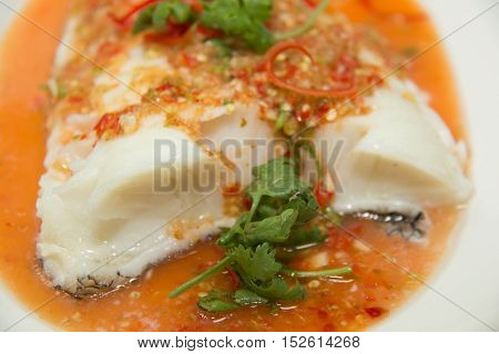 Steamed snow fish with spicy sauce on white dish
