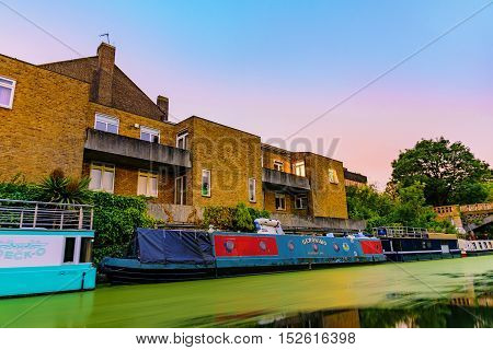 LONDON - JULY 16 2016: Riverside apartments with boat homes at night along the Regents Park canal which is a famous waterway on July 2016 in London.