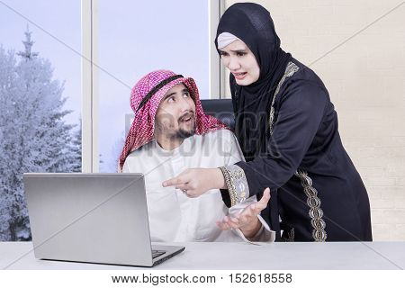 Arabian woman pointing at laptop with angry expression while her husband sitting in the living room