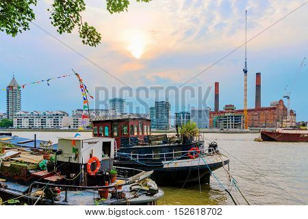 Riverside view of boats and Battersea power station in the distance