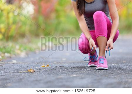 Running shoes woman runner tying shoe lace for run. Closeup of girl getting ready for jogging lacing sport shoe laces. Female sport fitness runner outdoors on forest path in spring fall season.