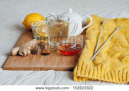 Herbal tea with chamomile flowers, turmeric and honey on a wooden board. Treatment of hot drink with ginger. Treatment of folk remedies in bed. Knitting needles and yarn for knitting.