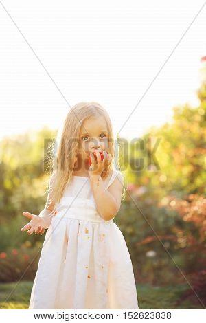 Nice little girl eating a tomato. She eats a vegetable. Girl soiled white dress in tomato juice. Sunset illuminates the flowing hair.