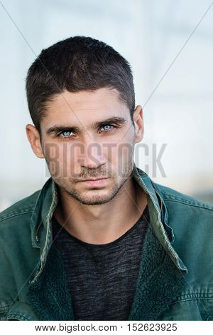 Portrait of a man with pale blue eyes. Men's beauty. Street fashion. Eyes like a Husky.