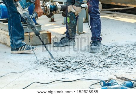 Builder worker with pneumatic hammer drill equipment breaking concrete at road construction site