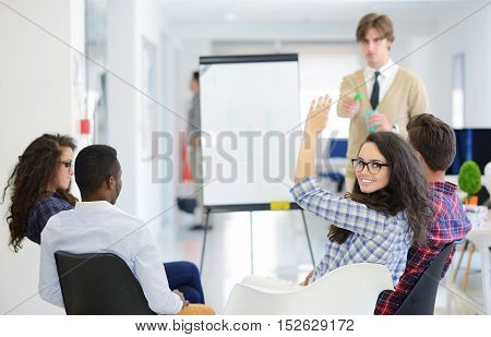 business education and office concept - serious business team with flip board in office discussing something