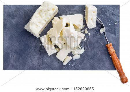 Top down close up view on fork and pieces of full fat white cows milk feta cheese from top down perspective