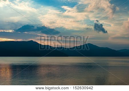 Caldera Lake On Dusk With Mountain Silhouettes On The Background