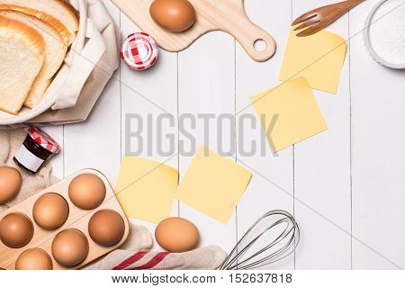 Eggs, milk and bread on white wooden background with Copy-space.