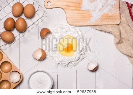 Egg in flour. Making dough background. Baking with raw eggs sugar flour milk