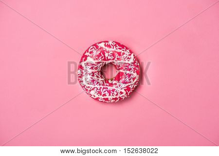 Donut with pink icing and sprinkles on pastel pink background. Sweet donut.