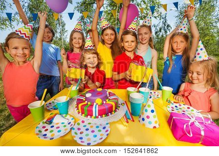 Big group of happy smiling kids in party hats at the outdoor birthday party