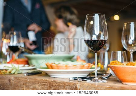 Wine glass on celebration table with people unfocused on background. Close up view.